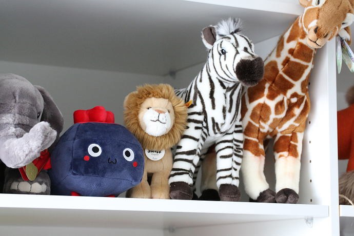 The plushie on a shelf with other stuffed animals.